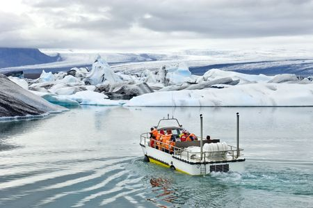 An amphibuous vehicle taking tourists for a cruise around the icebergs in the Jokulsarlon glacier lake, where huge chunks of ice from the Vatnajokull glacier float out to the Atlantic ocean photo
