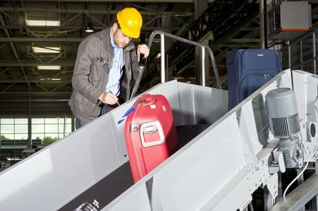 An airport security worker, manually checking luggage on a conveyor belt