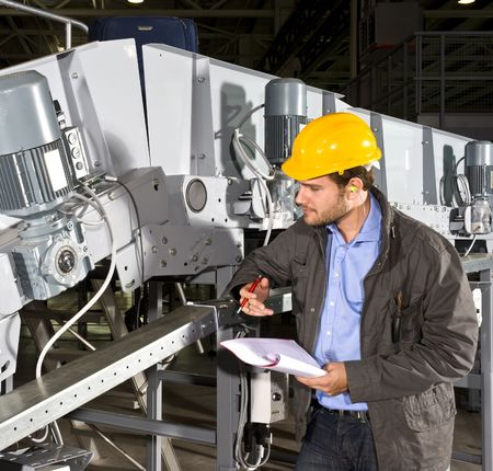 industrial machine: A maintenance engineer checking an industrial conveyor belt