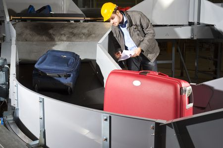 An airport official checking luggage on a conveyor belt, wearing a hard hat and earplugs