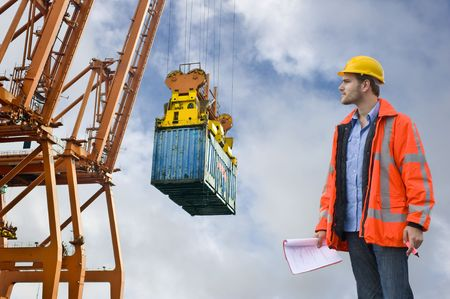 A Customs Control officer, checking the unloading of freight containers at an industrial harbor, wearing a hard hat and safety coat Stock Photo - 3577093