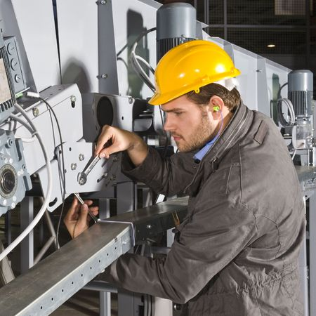 A male maintenance engineer at work on an industrial appliance photo