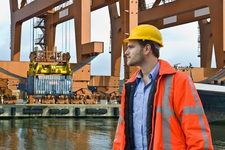 An engineer, closely watching the unloading of a constainer ship in a harbor environment photo