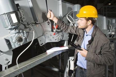 taschenlampe: Eine Installation Mechaniker workingon Industrie ein F�rderband Lizenzfreie Bilder