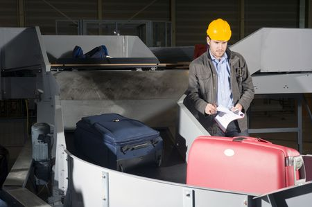 A security staff manually checking luggage after the airport security check at the luggage conveyor belts photo