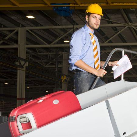 seguridad industrial: Un trabajador del aeropuerto con vistas a las cintas transportadoras utilizadas para la manipulaci�n de equipaje Foto de archivo