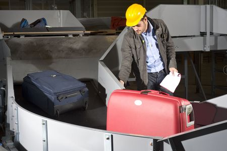 A maintenance engineer inspecting a luggage handling conveyor belt at an airport photo