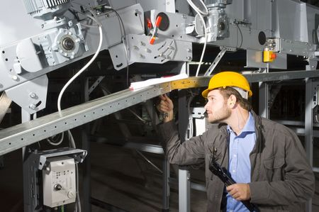 A maintenance engineer at work, tightening bolts of an industrial applience photo