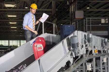 seguridad industrial: Un servicio de seguridad del aeropuerto superviser control de equipaje en una cinta transportadora Foto de archivo