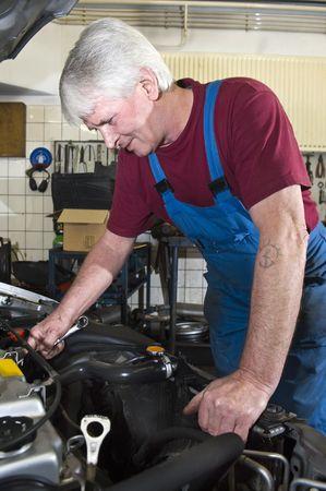 car inside: A senior motor mechanic servicing a car inside a garage