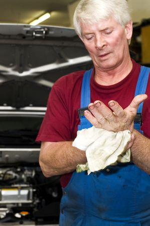 greasy: A motor mechanic, cleaning his greasy hands after servicing a car. Focus on his hands