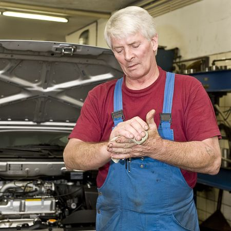 servicing: A motor mechanic cleaning his greasy hands after servicing a car. Focus on his hands Stock Photo