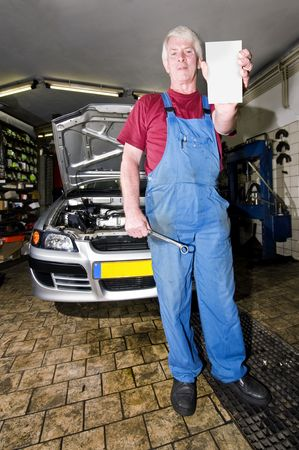 A senior motor mechanic, holding up a blank cart with a wrench in his hands, posing in front of the car he's been working on Stock Photo - 3733056