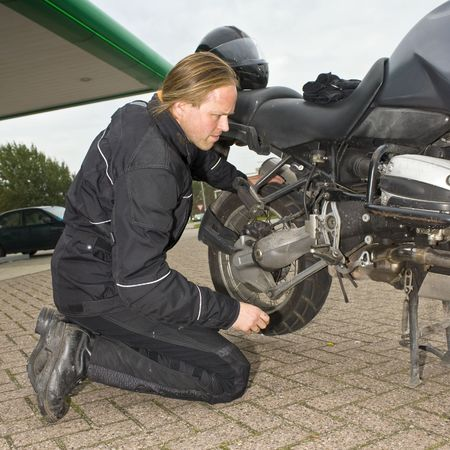 motorist: A motorist having problems and checking his motorcycle