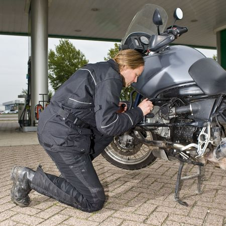 motorist: A motorist checking the oil level of his motorbike at a gas station
