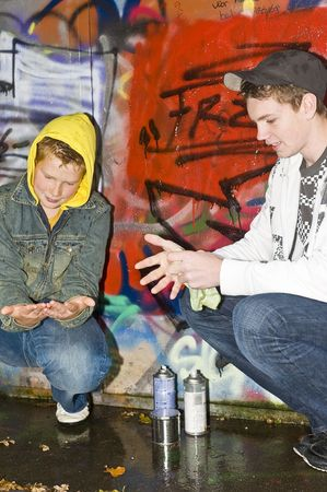 hooded vest: Two boys, outdoors, cleaning their hands from paint.