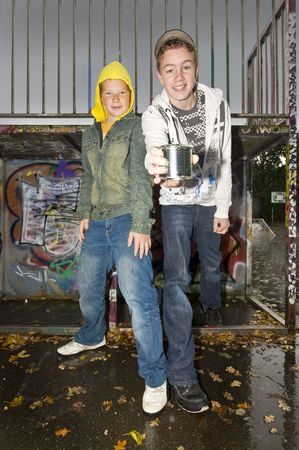 Two boys outdours, in autumn, showing a tin can. photo