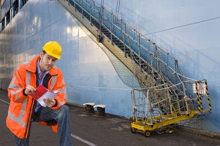 ship bow: A man, wearing a reflective safety coat and a hard hat, ready to check the boarding list with crew names of a huge container ship