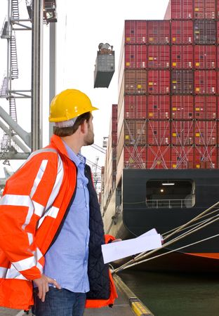 inspection: Harbor employee overseeing the loading of a huge container ship