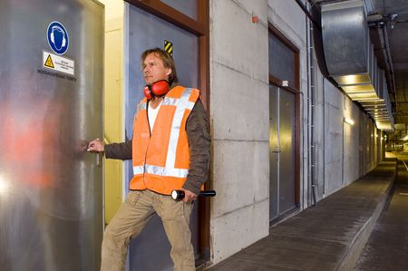 dimly: A sturdy looking engineer, opening a door to an engine room in a dimly lit tram tunnel, ignoring the safety precaution to wear his ear protection