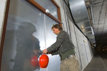 A man with a hard hat in his hand unlocking a steel door inside a tunnel photo