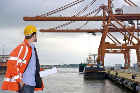 A man wearing a safety coat and a hard hat inspecting the huge cranes at a container harbor photo