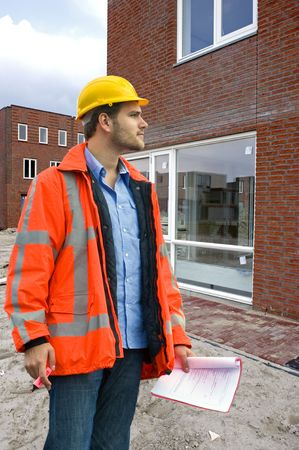 A building inspector visiting a construction site with a checklist in his hand photo