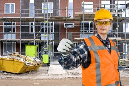 A satisfied looking construction worker giving a thumbs-up in front of a huge residential building site photo