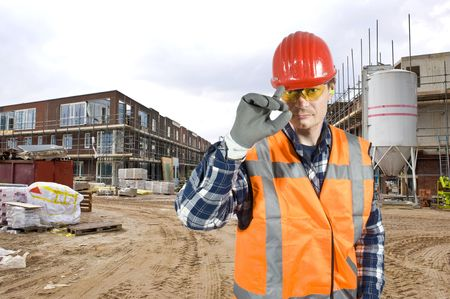 A friendly looking construction worker touching his hard hat with is finger in salute of the customer photo