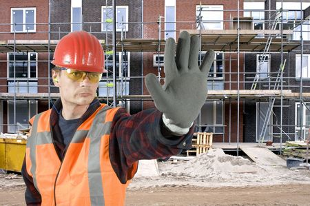 A serious looking construction worker giving a stop signal with his hand in front of a huge residential building site photo