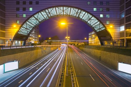 bridging: An inner city highway at night with an office building, bridging the traffic Stock Photo