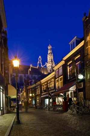 cobble: Una strada di pietra cobble con ristoranti e negozi leding verso il campanile illuminato di una grande chiesa di notte