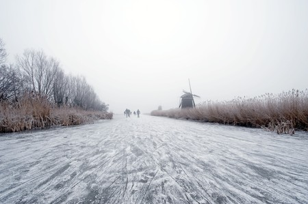 archetypal: The archetypal Dutch winter on a foggy morning on a frozen canal surrounded by reed, willows, windmills and a handful of ice skaters approaching in the distance