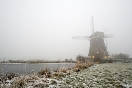 ice dam: A typical Dutch windmill on a foggy winter morning with ice covered canals, and a frozen dyke