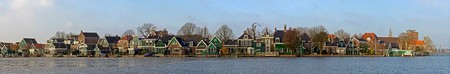 The old, picturesque houses of Zaanse Schans along the river side of the Zaan on a cold winter morning photo