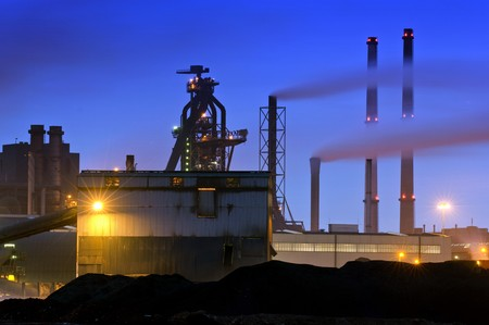 menacing: The menacing outline of a blast furnace, surrounded by chimneys and the industrial appliances of a steel plant at night