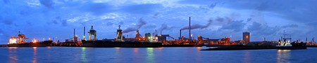 steelworks: A panorama of a steel plant at twilight with huge ships being unloaded from their freight of iron ore and coal Stock Photo