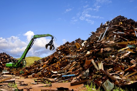 scrap heap: A green digger, used to move metal scrap Stock Photo