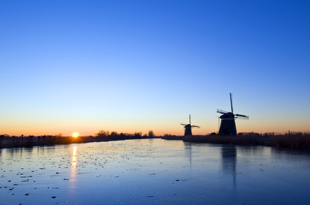 The sun rises over rural holland in wintertime, with windmills and an ice covered, frozen, canal Stock Photo - 4103837