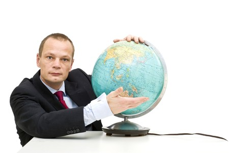 emerging markets: A businessman wearing a suit presenting an oldfashioned globe, with Asia in front, illustrating emerging markets