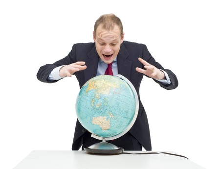 emerging markets: A businessman, hovering over a globe as if if looking at a fortune tellers sphere, seeing the possibilities and potential of emerging markets and global business Stock Photo