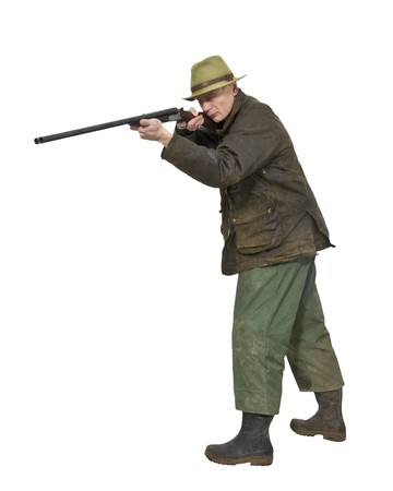 A hunter aiming a side by side shotgun wearing a hat, waxcoat, muddy rain pants and rubber boots