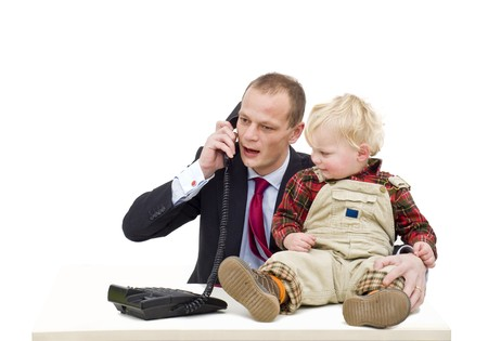 A working father on the phone, whilst caring for his toddler boy, a conceptual image for the contemporary emancipation, where fathers are taking care of their kids and maintaining a professional career photo