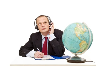 A businessman with a head set on listening attentively to a conversation in another language, represented by the globe on his desk photo