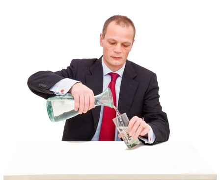 A businessman pouring a glass of water behind a desk photo