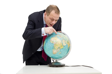discovering: A businessman discovering the potential of global business, visualised by his expression and pointing finger on the globe on the table in front of him. Stock Photo