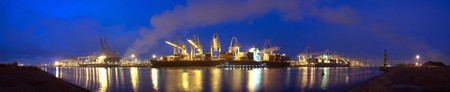 A panoramic image of  three container ships being unloaded at night at a busy commercial harbour, with a small trawler moored alongside.  photo