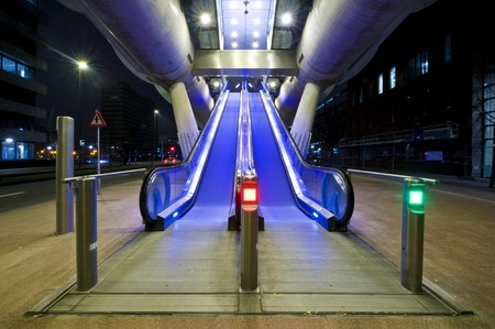 elevated: Two escalators, leading up towards the entrance of the platform of an elevated tram line