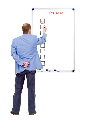 A business man checking off his completed tasks from a to do list, written on a whiteboard photo