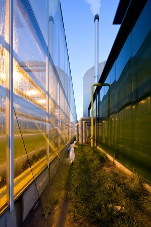 The exterior glass fascade of a huge glasshouse with heating system and generator photo